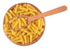 在一个木碗的未煮过的意大利面团fusilli在白色 库存图片
