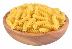 在一个木碗的未煮过的意大利面团fusilli在白色 免版税库存图片