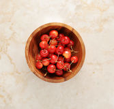 在一个木碗的樱桃在大理石背景 免版税图库摄影