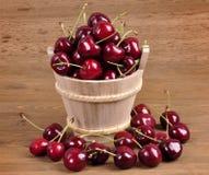 在一个木碗的樱桃在木背景 免版税库存图片