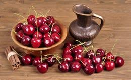 在一个木碗的樱桃有汁液的一个碗的在木背景 图库摄影