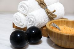 在一个木碗的橙色腌制槽用食盐和在一个木立场和黑色卞石头的三块白色毛巾在一张白色大理石桌上站立 库存图片