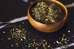 在一个木碗的清凉茶在黑大理石背景 免版税图库摄影