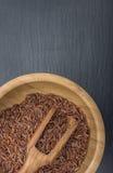 在一个木碗的红色米和橄榄木瓢在板岩或石头黑背景  库存照片