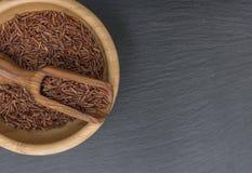 在一个木碗的红色米和橄榄木瓢在板岩或石头黑背景  免版税库存图片