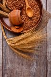 在一个木碗的荞麦在麦子附近分支的木背景  垂直的图象 免版税库存图片