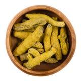 在一个木碗的被处理的姜黄根茎在白色 库存图片