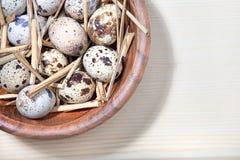在一个木碗的鹌鹑蛋和秸杆在木表 免版税库存图片