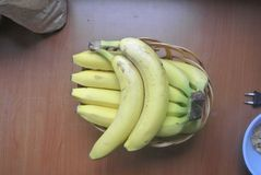 在一个木碗的黄色香蕉在一张木桌上 图库摄影