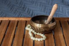 在一个木立场的西藏唱歌碗和玉小珠 免版税库存图片