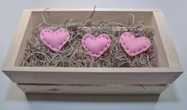 在一个木箱的三桃红色布料心脏 图库摄影