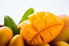 在一个木箱的新和美好的芒果果子集合有在白色背景隔绝的被切的切成小方块的芒果大块的,拷贝空间 图库摄影