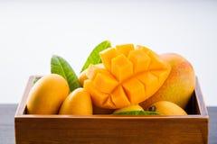 在一个木箱的新和美好的芒果果子集合有在白色背景隔绝的被切的切成小方块的芒果大块的,拷贝空间 免版税图库摄影