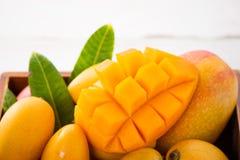 在一个木箱的新和美好的芒果果子集合有在轻的木背景的被切的切成小方块的芒果大块的, 免版税库存图片