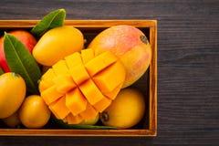 在一个木箱的新和美好的芒果果子集合有在黑暗的木背景,拷贝空间的被切的切成小方块的芒果大块的 免版税库存照片