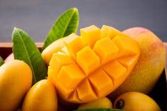 在一个木箱的新和美好的芒果果子集合有在黑暗的木背景,拷贝空间的被切的切成小方块的芒果大块的 库存照片