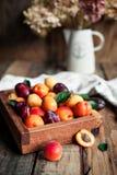 在一个木箱的新鲜的杏子在葡萄酒背景 图库摄影