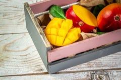 在一个木箱的著名亚尔方索芒果切片在木背景,顶视图 复制空间 免版税库存照片