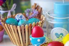 在一个木篮子和烛台的塞思复活节彩蛋有蜡烛的 库存图片
