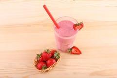 在一个木篮子和玻璃的水多的草莓有很多在浅褐色的木背景的桃红色酸奶 在玻璃的圆滑的人 免版税库存照片