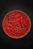 在一个木篮子的明亮的红浆果在黑背景 五颜六色的红色潮流 成熟和鲜美红色潮流一张顶视图  图库摄影