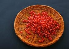 在一个木篮子的明亮的红浆果在黑背景 充分条板箱莓果 酸和水多的红色潮流一张顶视图  免版税库存照片
