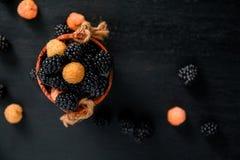 在一个木篮子的黑和黄色莓在背景 框架 复制空间 顶视图 库存图片