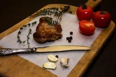 在一个木老切板的水多的牛排用香料和菜 在文本设计的黑背景为 免版税图库摄影