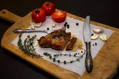 在一个木老切板的水多的牛排用香料和菜 在文本设计的黑背景为 图库摄影