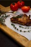 在一个木老切板的水多的牛排用香料和菜 在文本设计的黑背景为 免版税库存照片