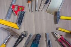 在一个木背景的不同的工具 锤子,钻子,钳子 螺丝刀,统治者,切开钳子 免版税库存照片