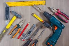 在一个木背景的不同的工具 锤子,钻子,钳子 螺丝刀,统治者,切开钳子 免版税库存图片