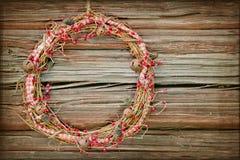 在一个木背景的红色圣诞节花圈 免版税库存图片