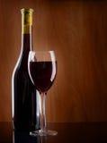 在一个木背景的红葡萄酒玻璃和瓶 免版税库存图片