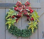 在一个木门的圣诞节花圈 库存照片