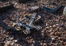 在一个未玷污的坟墓的下落的金属十字架 免版税库存图片
