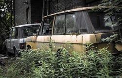 在一个杂乱后院的被放弃的打破的汽车 库存照片