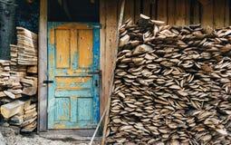 在一个村庄存贮房子的看法工具和火森林的 葡萄酒在蓝色颜色的被绘的门 绘部分地pilled  库存照片