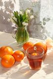 在一个杯子、报春花和柠檬的茶在一张晴朗的桌上 免版税库存图片