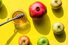在一个杯子、石榴和苹果的蜂蜜犹太新年 库存图片