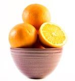 在一个杯子的三个恰好色的桔子在白色背景-前面和后面切成了两半 免版税图库摄影