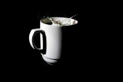 在一个杯子的下落牛奶 免版税库存图片