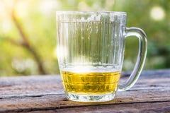在一个杯子的啤酒在户外木桌上 图库摄影