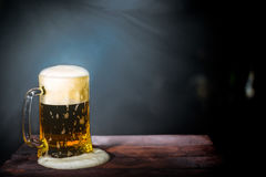 在一个杯子的啤酒在黑暗的背景 库存照片