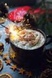 在一个杯子的圣诞节闪烁发光物热巧克力或可可粉用蛋白软糖,干桔子,桂香,毛皮树,手套在黑暗的石ba 库存照片