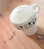 在一个杯子的奶粉在木背景 免版税库存照片