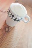 在一个杯子的奶粉在木背景 免版税库存图片