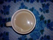 在一个杯子的布朗咖啡在蓝色桌上 库存照片