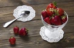 在一个杯子的成熟草莓冰淇凌和茶匙在餐巾 免版税库存图片