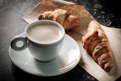 在一个杯子的早晨浓咖啡在一张桌上用后边新月形面包 免版税库存照片
